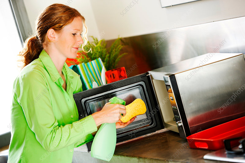 Woman cleaning microwave oven