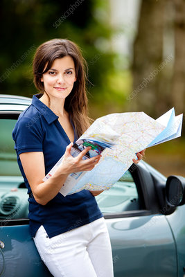 Woman driver reading a road map