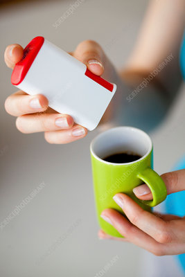 Woman adding artificial sweetener