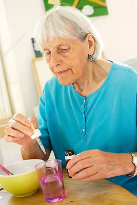 Elderly woman taking medication