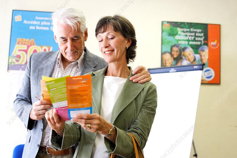 Senior couple reading brochure
