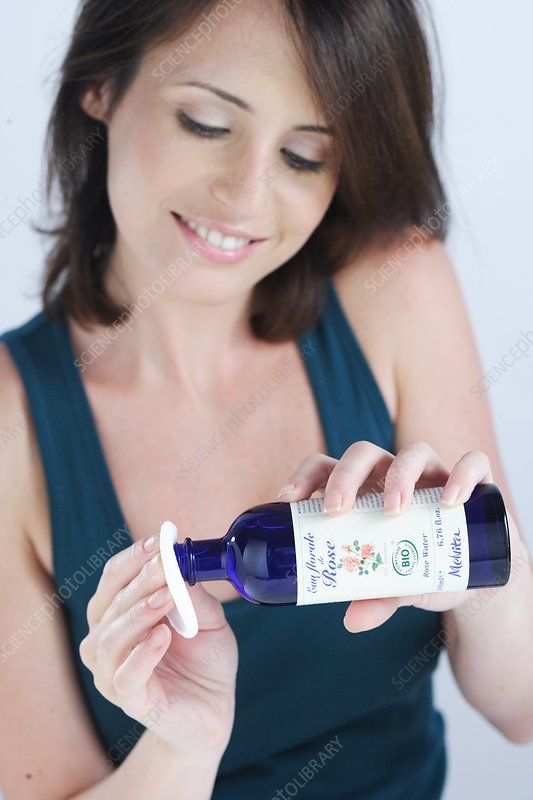 Woman using rose water lotion