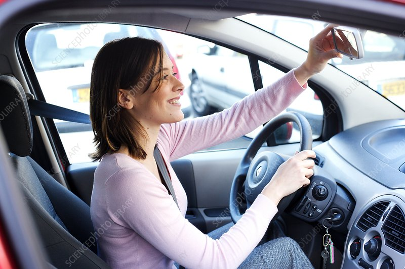 Woman adjusting rear-view mirror