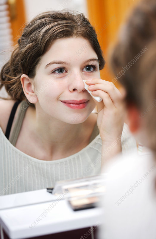 Teenager cleaning her face
