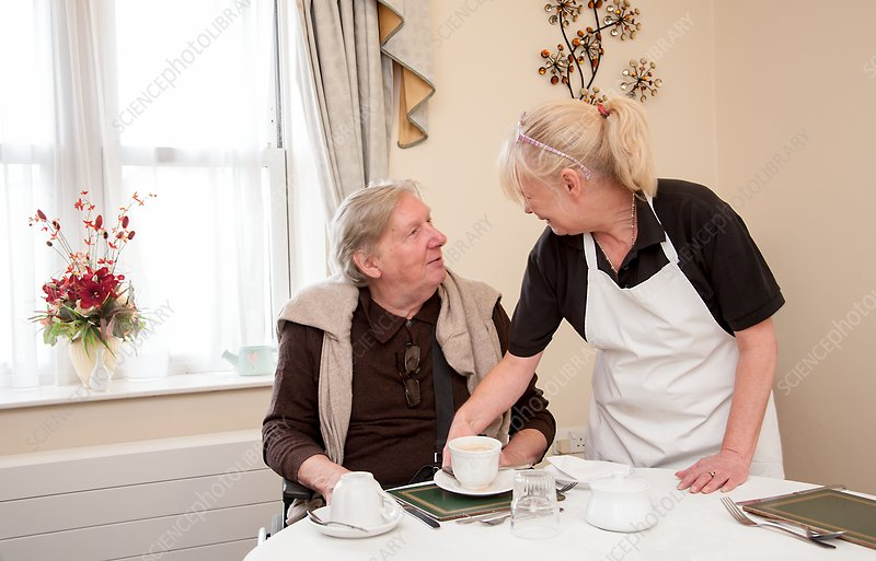 Care home resident being served tea