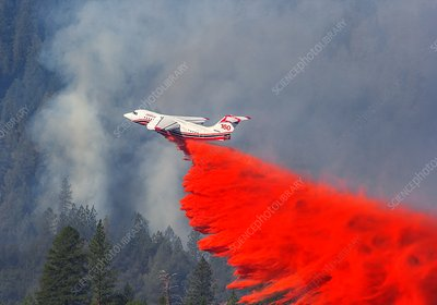 Aircraft releases fire retardant over forest fire
