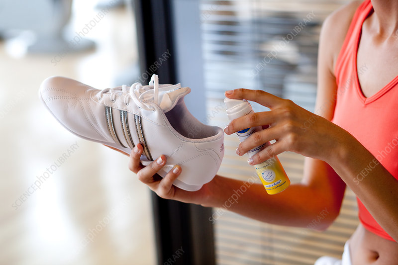 Woman applying shoe spray