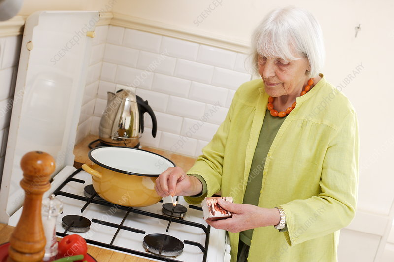 Elderly woman using gas burner