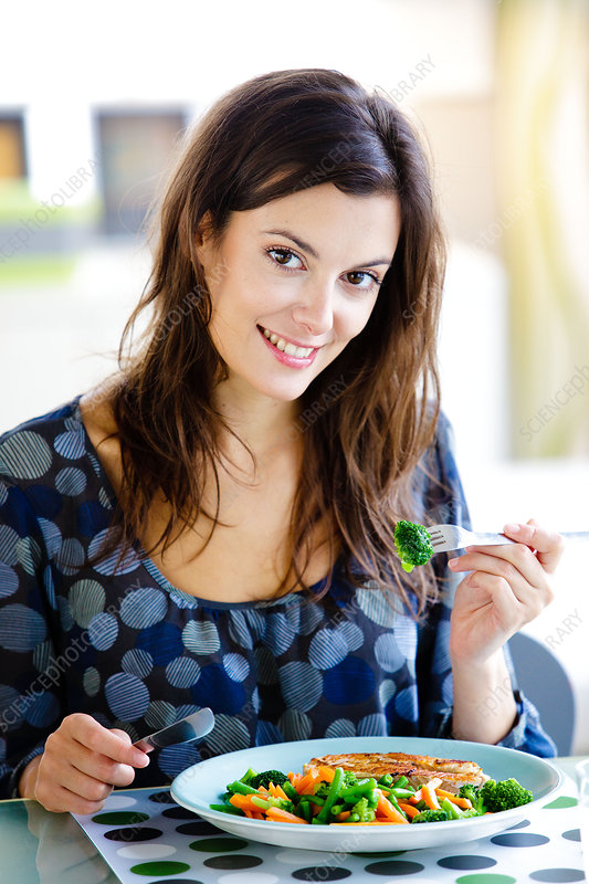 Woman eating fish and vegetables
