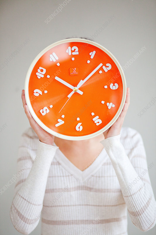 Woman holding orange clock