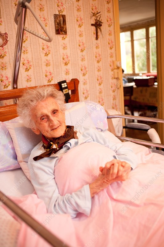 Elderly woman in medical bed at home