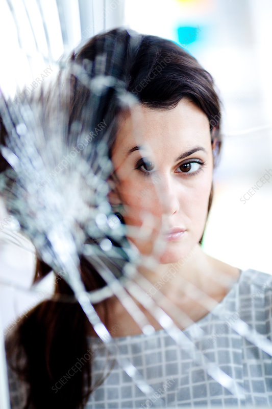 Woman in front of a broken mirror