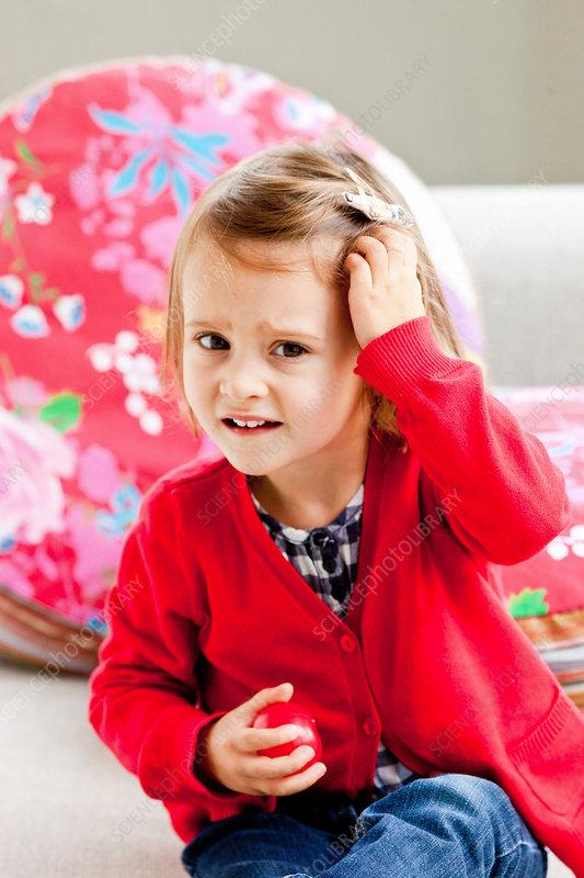Child scratching her scalp