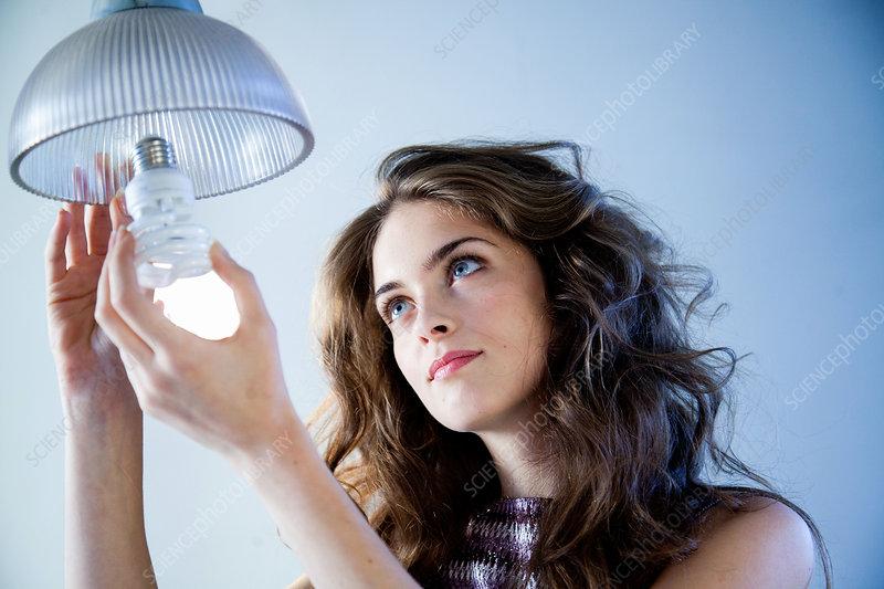 Woman using energy saving bulb