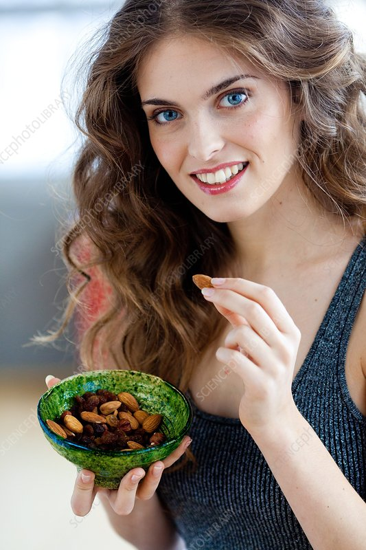 Woman eating several nuts