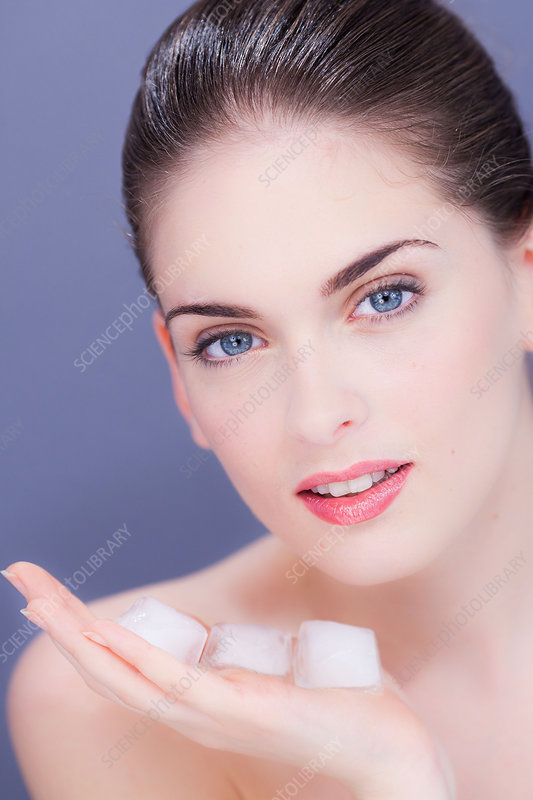 Woman applying ice cubes on face