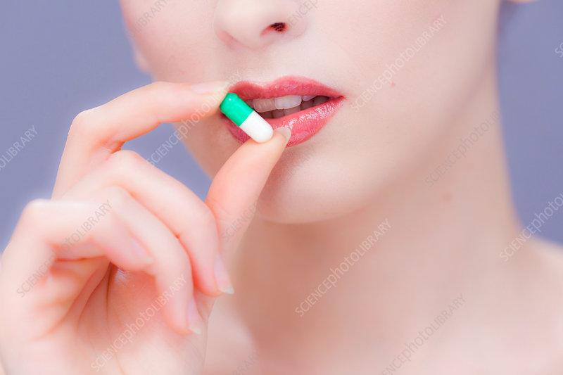 Woman taking capsule