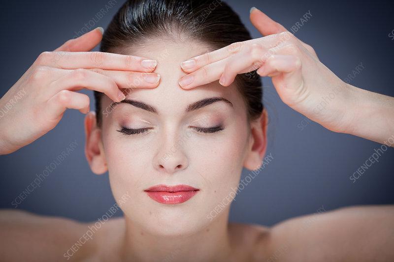 Woman massaging forehead