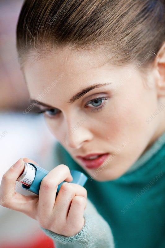 Woman using an aerosol inhaler