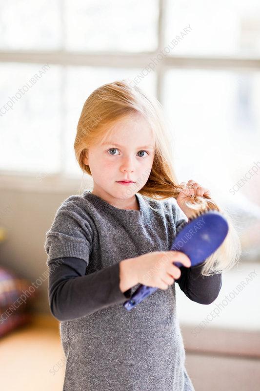 7 year old girl brushing her hair