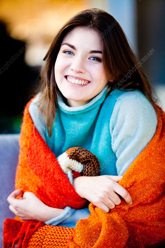 Smiling woman wrapped in blanket