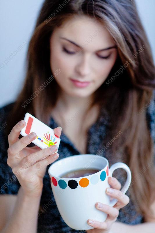 Woman using artificial sugar