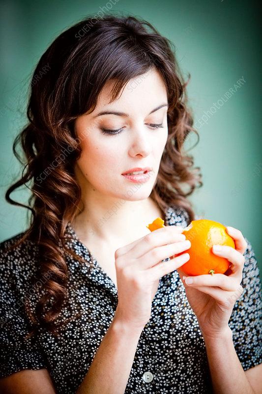Woman peeling an orange