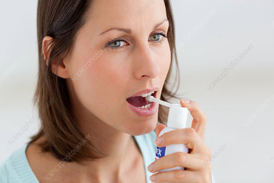 Woman using spray for sore throat