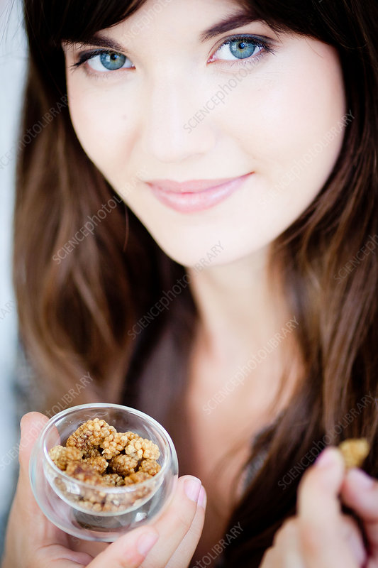 Woman eating dried mulberries