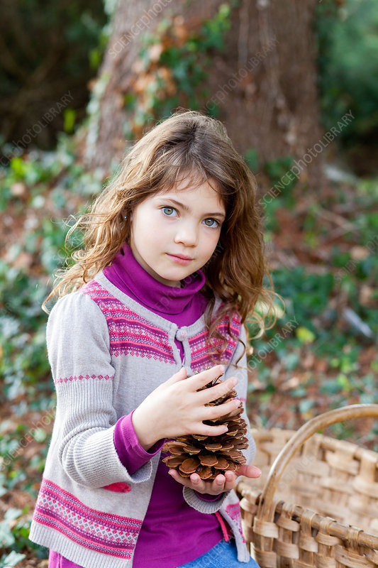 Girl picking up pine cones