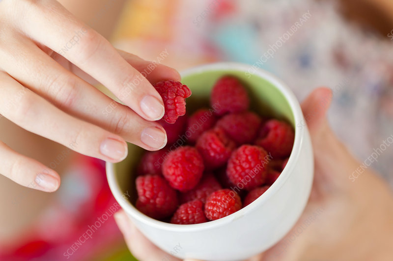 Woman eating raspberries