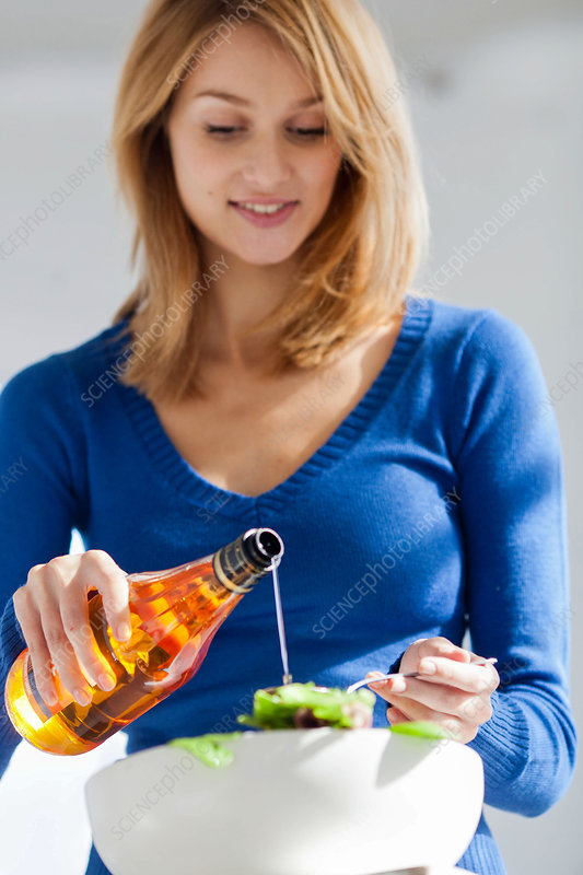 Woman adding cider vinegar on a salad