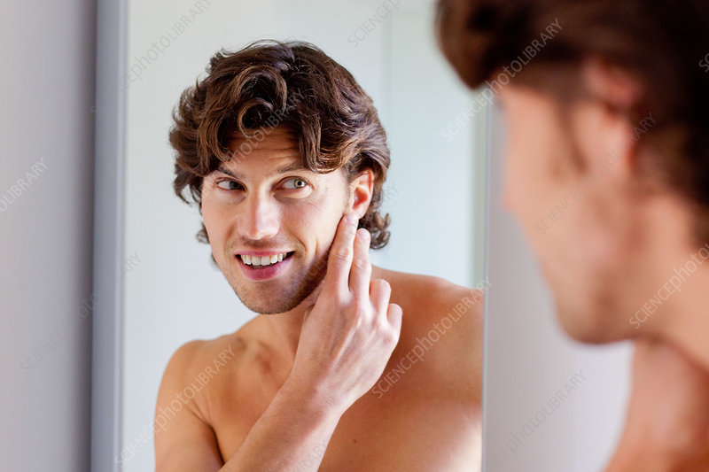 Man checking his face in mirror