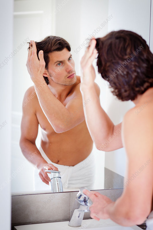 Man inspecting his hair in a mirror