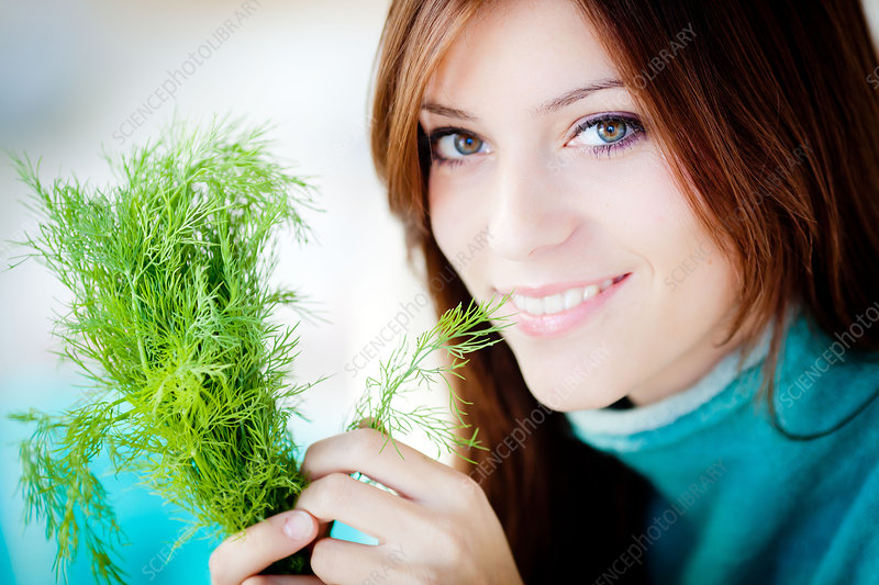Woman smelling dill