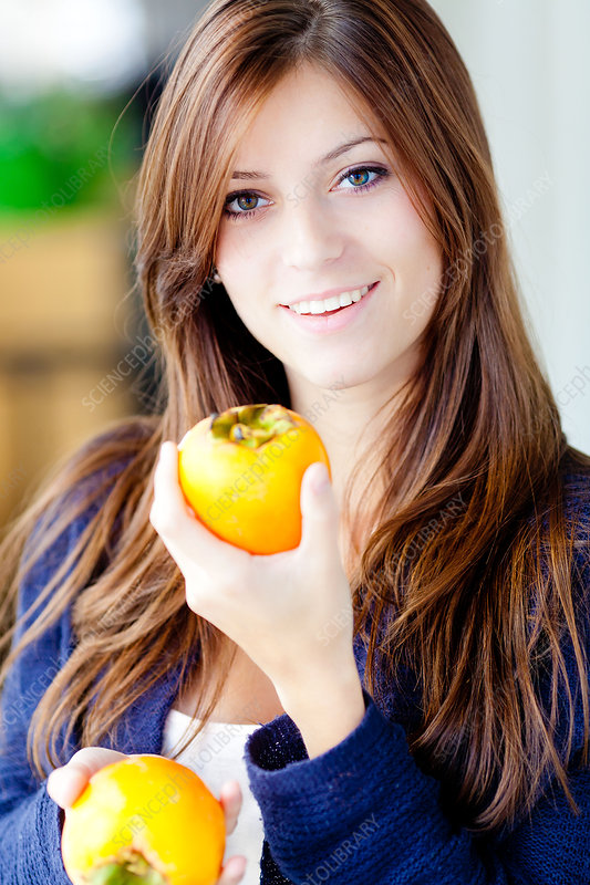 Woman eating persimmon
