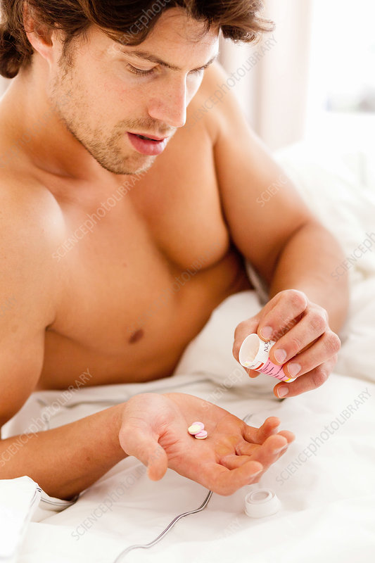 Man in bed taking pills