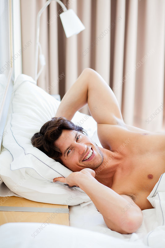Man waking up and stretching in bed