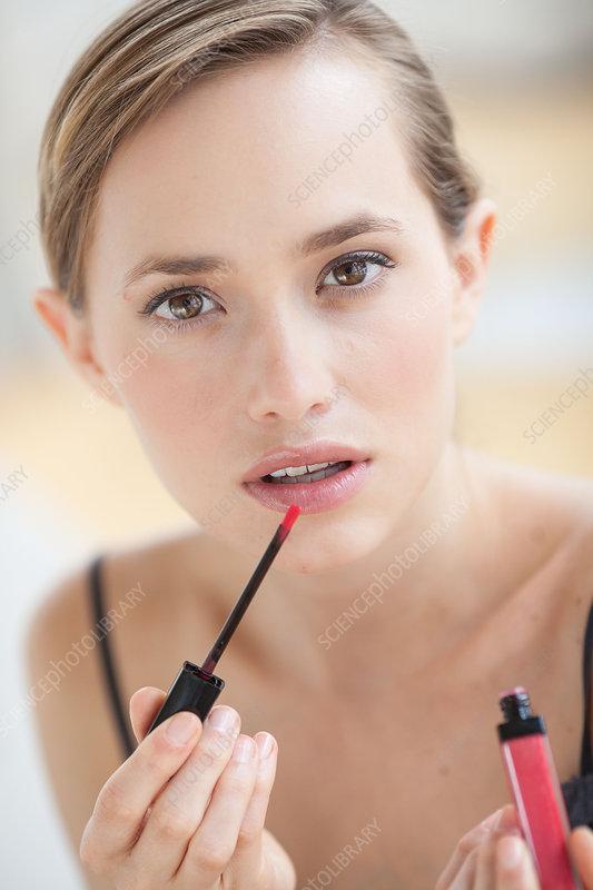 Woman applying gloss