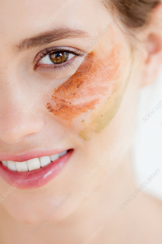 Woman applying clay beauty mask