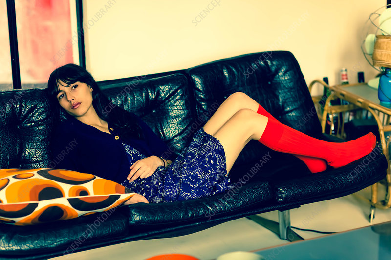 Woman lying on a leather couch
