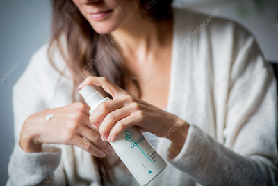 Woman applying oestrogen gel