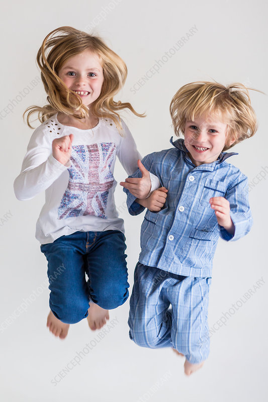 Sister and brother jumping on bed