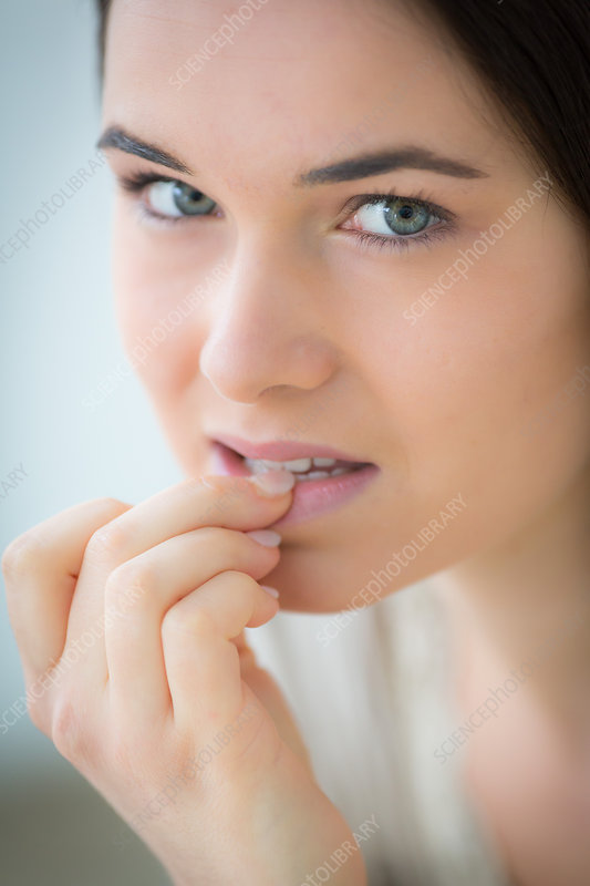 Woman chewing her thumbnail