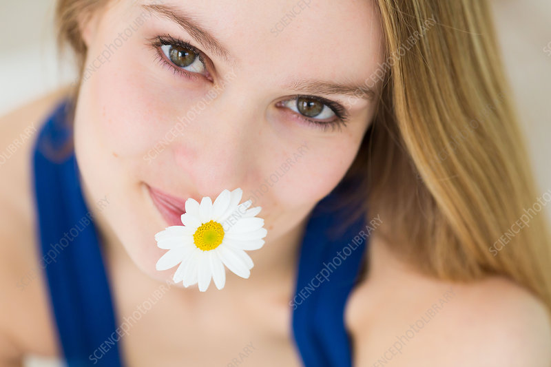 Woman holding a daisy in her mouth