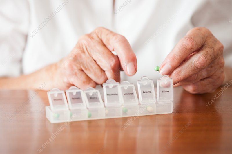 Elderly woman using a pill box