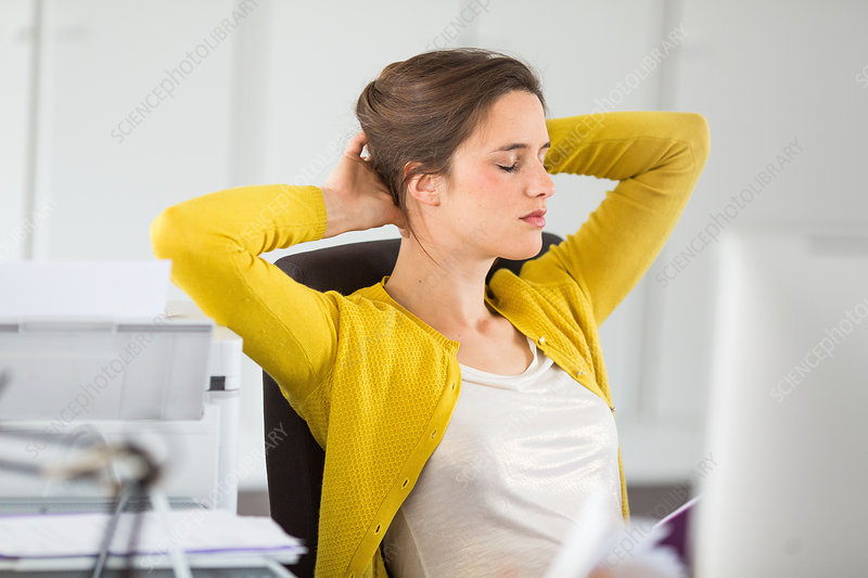 Woman relaxing and stretching arms at work