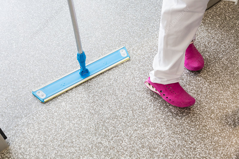 Cleaner mopping a hospital ward floor
