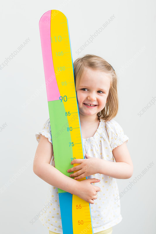 3-year-old girl holding a height gauge