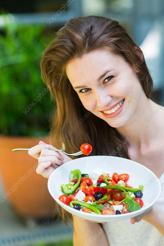 Woman eating a Mediterranean salad